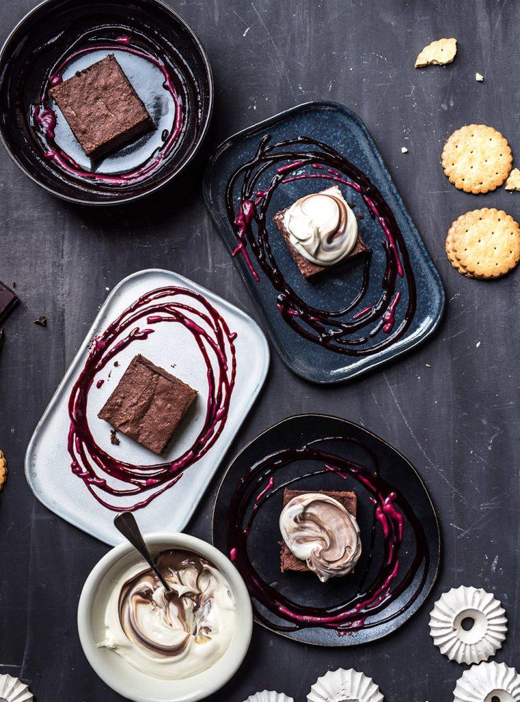 Dessert mit Schokokuchen, Crème Fraîche, Baiser, Cassis und einem Hauch Fleur de Sel