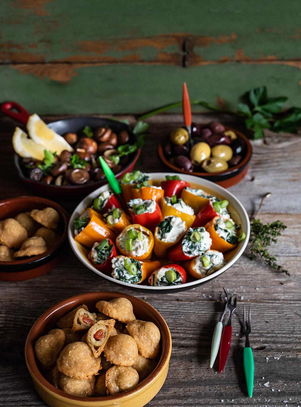 Gebratene Champignons mit Knoblauch, knusprig gebackene Oliven und Mini-Paprikas mit Ziegenfrischkäse
